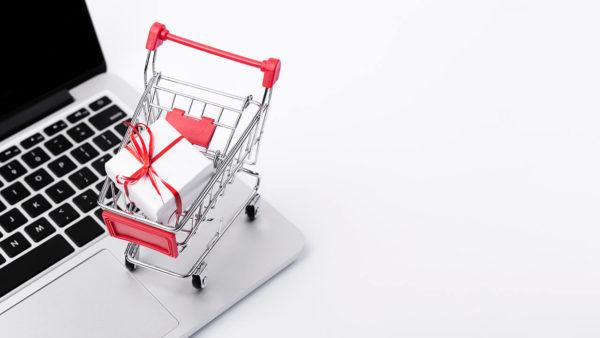 Carrinho de compras na frente de um notebook representando abordagem de vendas eficiente