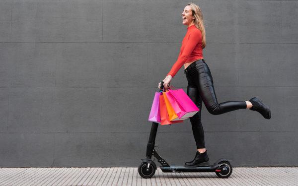 Cliente feliz de patinete e com sacolas de compras. Cliente satisfeita por conta de uma boa abordagem de vendas