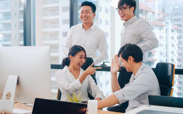 Grupo de jovens de negócio comemorando aumento na retenção-de-clientes